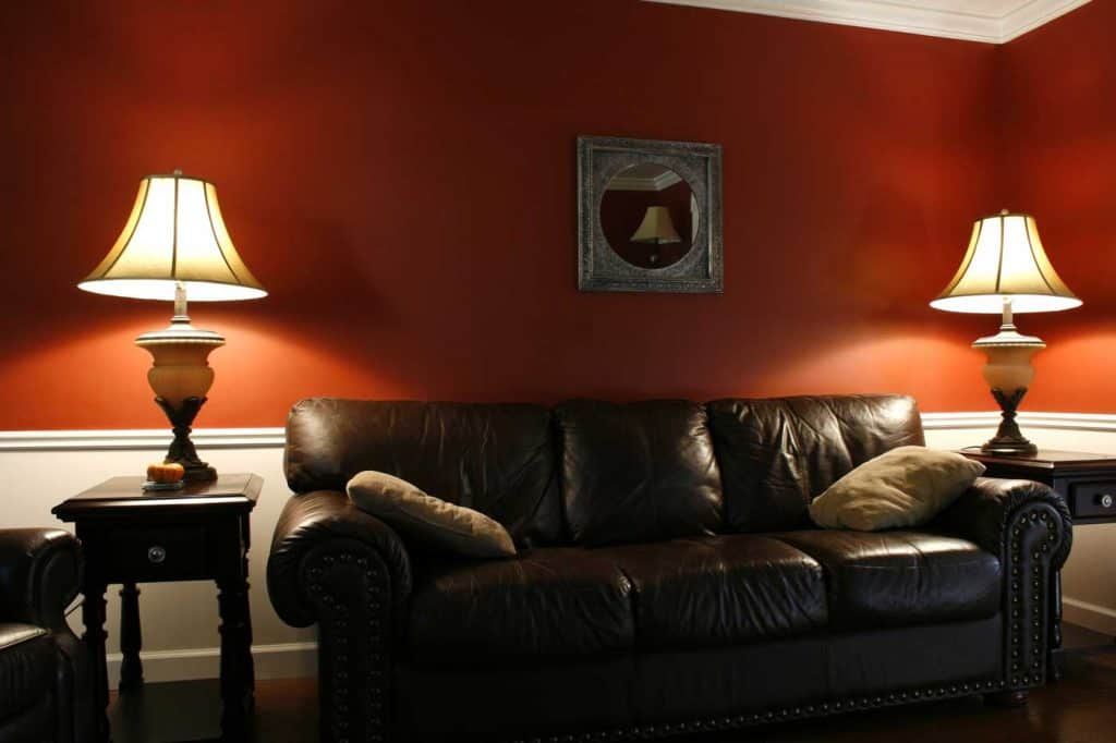 Orange wall living room with a dark brown leather sofa
