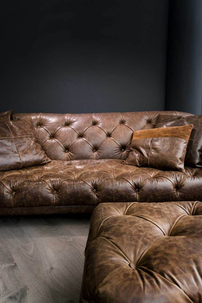Detail of Vintage dark Brown Leather Sofa in a modern living room and big Black Empty Wall for copy space over the sofa.
