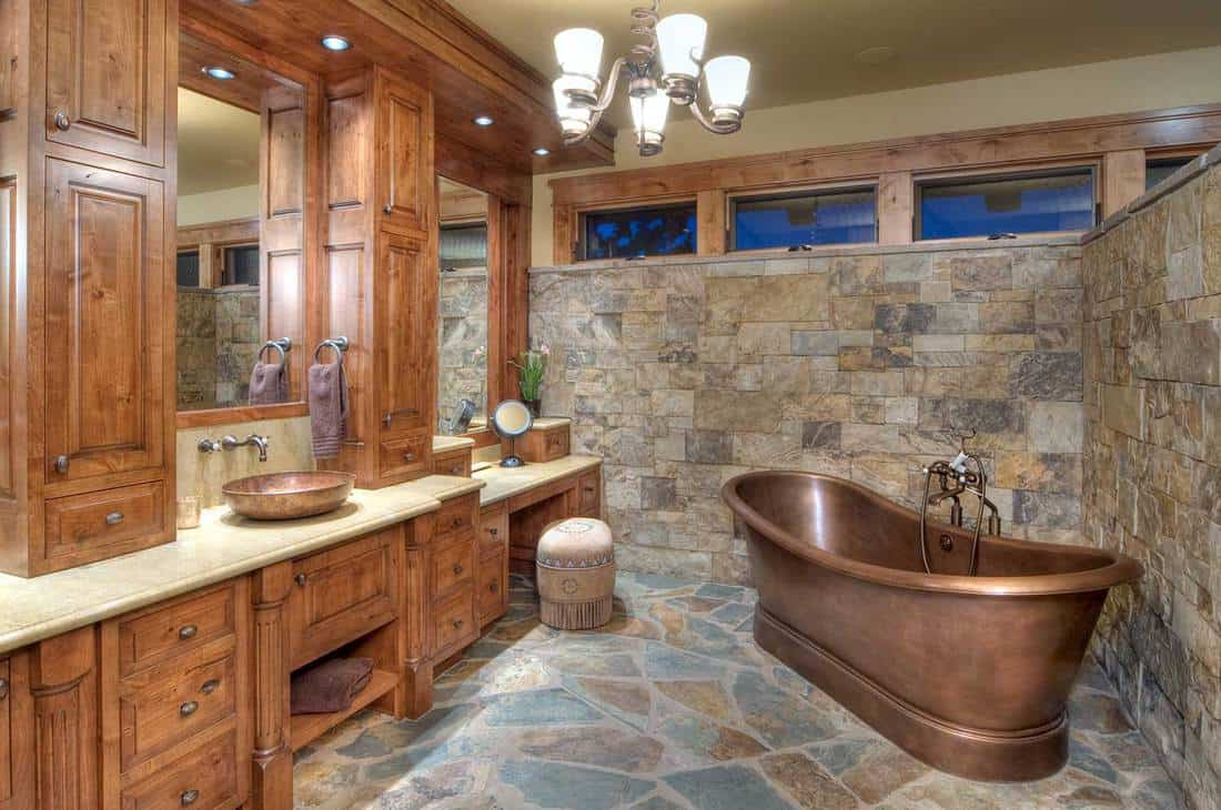 Elegant bathroom with copper bathtub and a copper sink