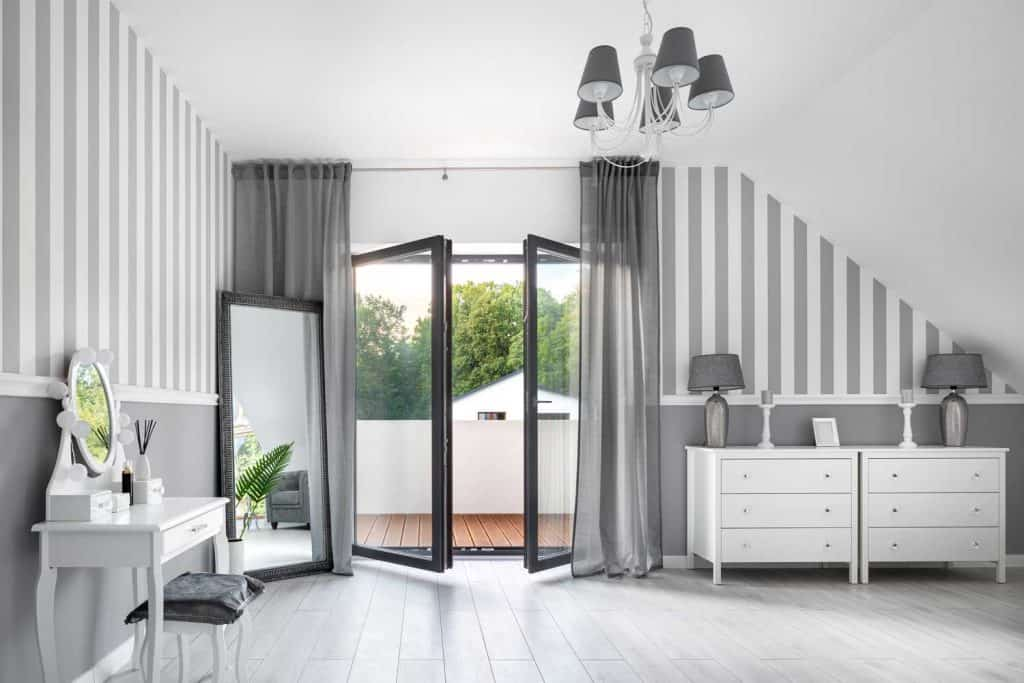 Gray room with white furniture and a large floor mirror with black bezels