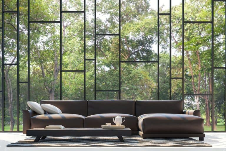 Huge couch near huge window and trees on the background, 13 Fantastic Couches for Tall People