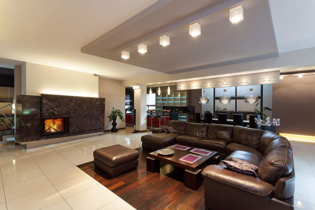 Huge living room with curved sofa and a fireplace with decorative stones for design