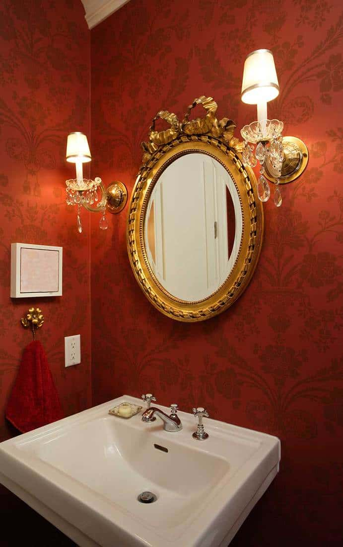 Interior of modern residence bathroom with red decorated walls, sink and gold framed mirror