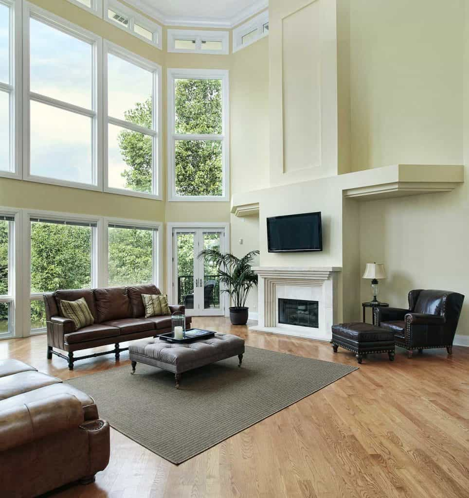 Large Living room with two story windows featuring dark brown leather sofas