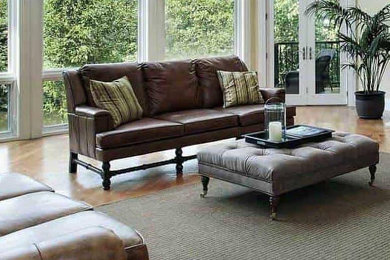 Living room interior with dark brown leather sofa, large glass windows and cushion table, 17 Dark Brown Leather Sofa Decorating Ideas