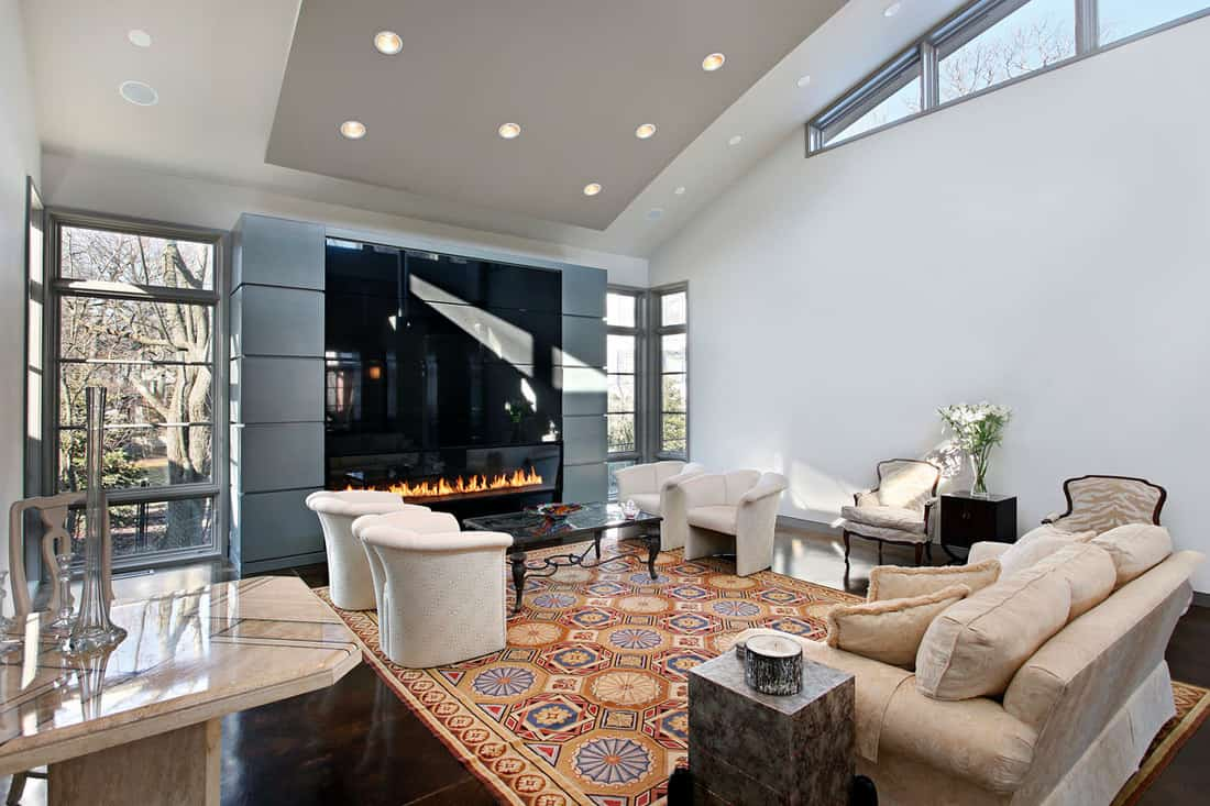 Living room with a gorgeous fireplace with TV set and a dirty white colored sofa