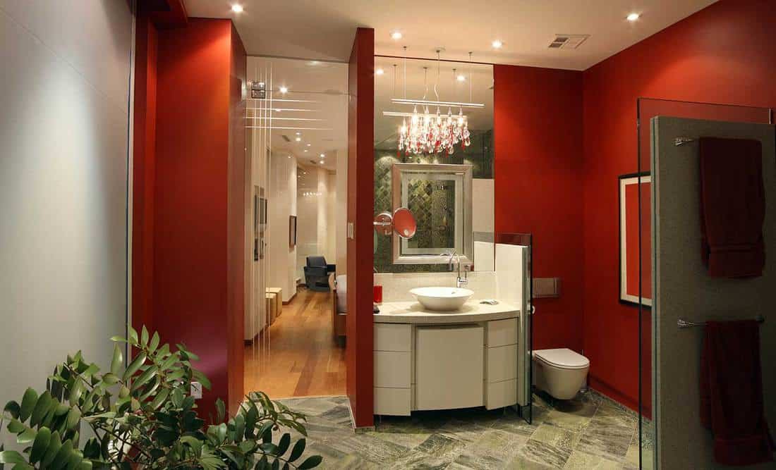 Luxury bathroom with chandelier on sink cabinet, red walls, toilet and large mirror