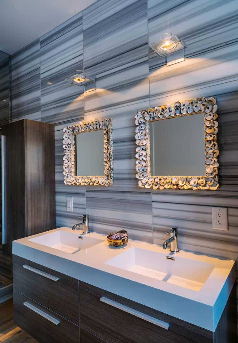 Luxury main bathroom interior with double sink vanity area and seashell decorated mirrors
