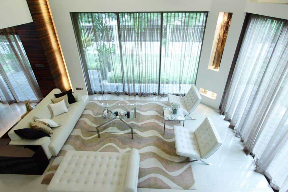 A stylish and modern living room with white sheer curtains