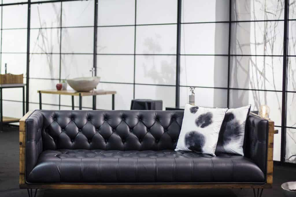 Modern standalone dark brown black leather sofa with wooden accents in a loft type living room