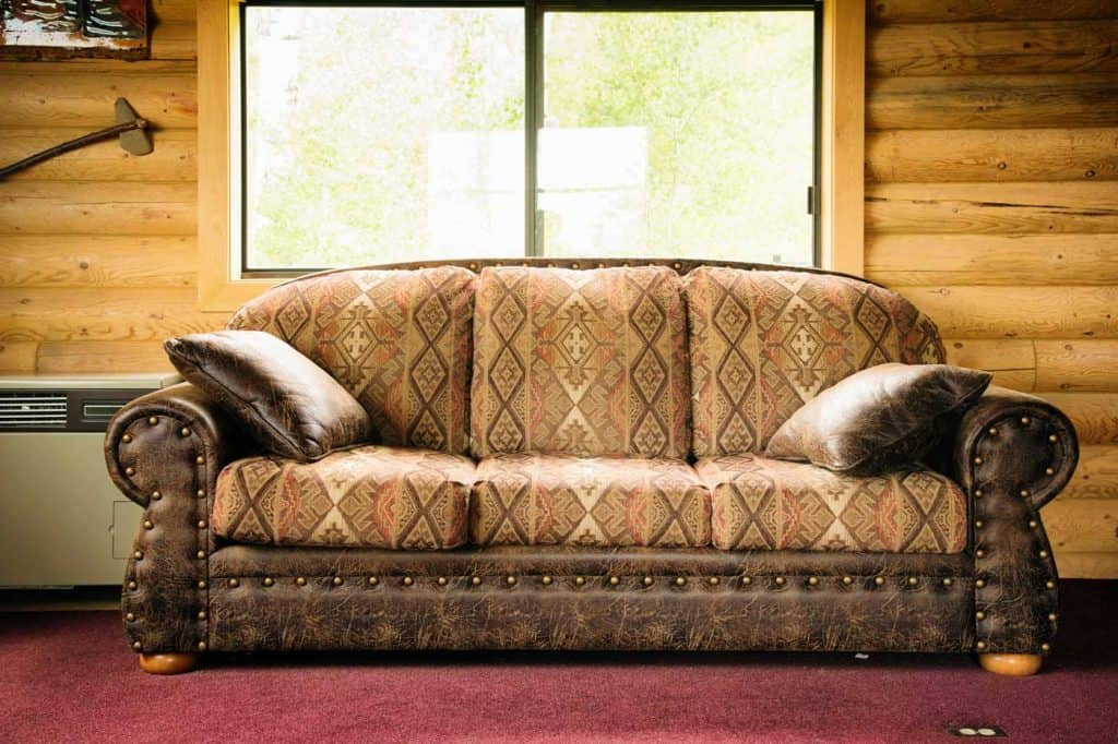 Native american inspired dark brown leather sofa with light patterned cushions, in log cabin under a window.