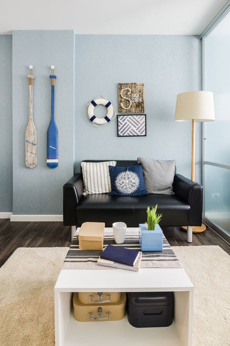 Nautical themed living room with black couch and white table
