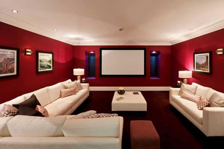 Red Velvet colored wall with pictures hanged and dirty white couch, 21 Wall Decor Ideas For Basement