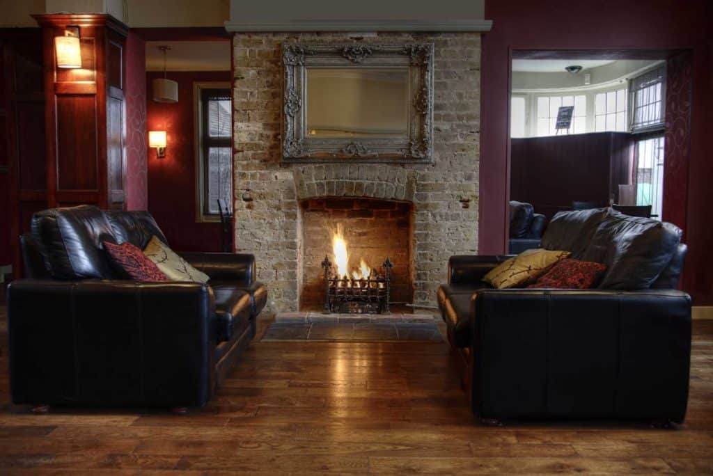 Room with dark brown leather sofas and an open fireplace.