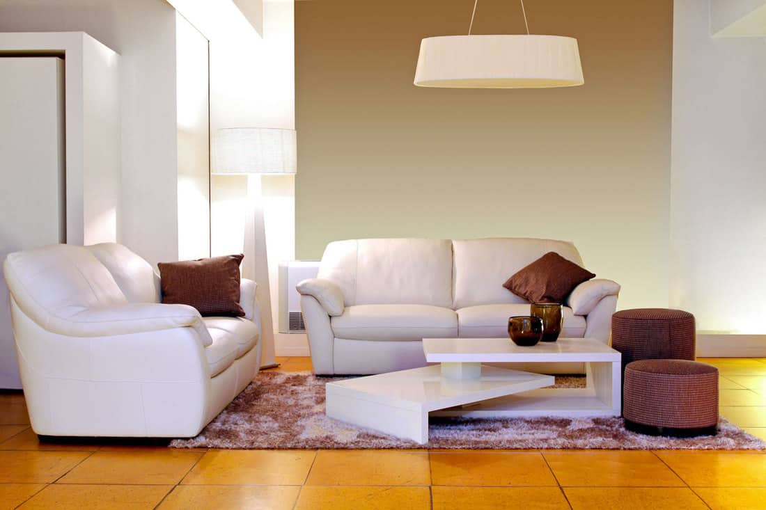 White colored sofas with matching yellow tiles and brown poufs on the side
