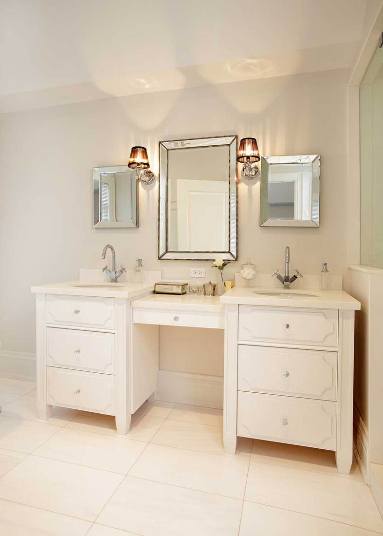 White luxury bathroom with double sink cabinets and mirrors