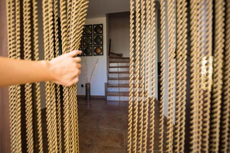 Woman shoving gold beaded curtain at doorway, 10 Fantastic Indoor Beaded Curtains For Doorways