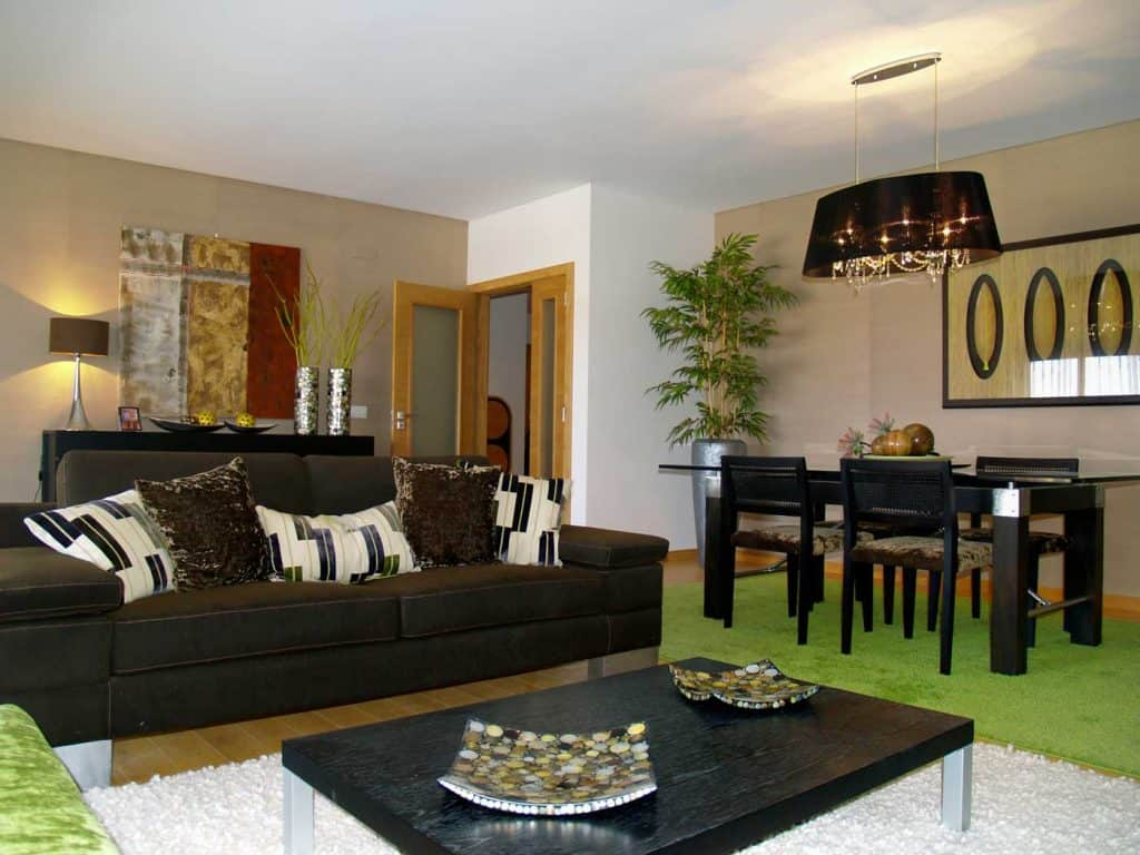 living room with dark brown leather sofa adjacent to a rectangle dining table on green rug