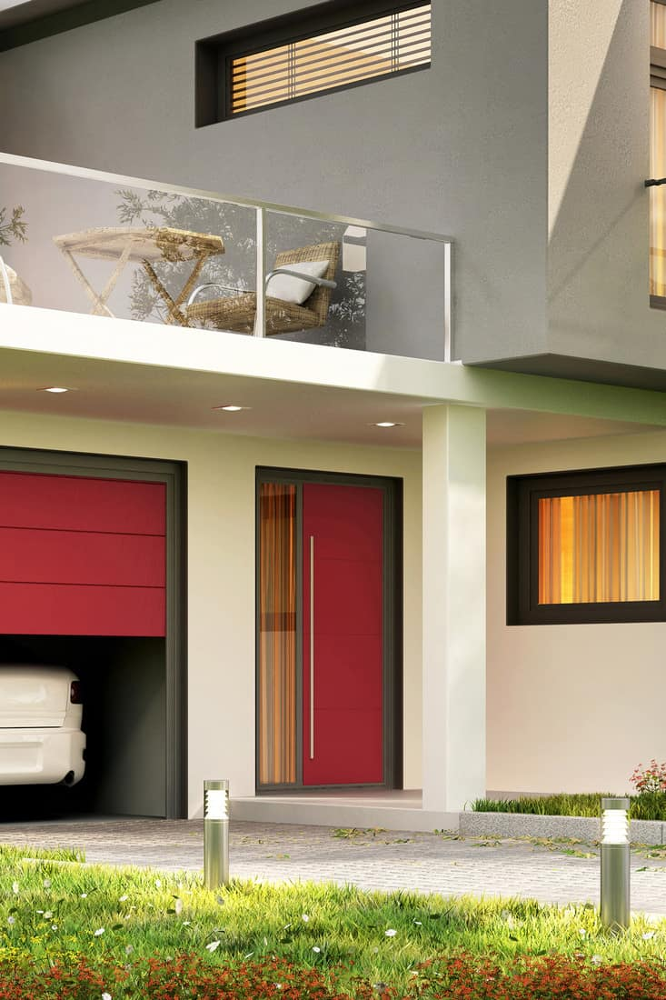 A modern luxurious house with a red front door, red garage door, and seamless windows