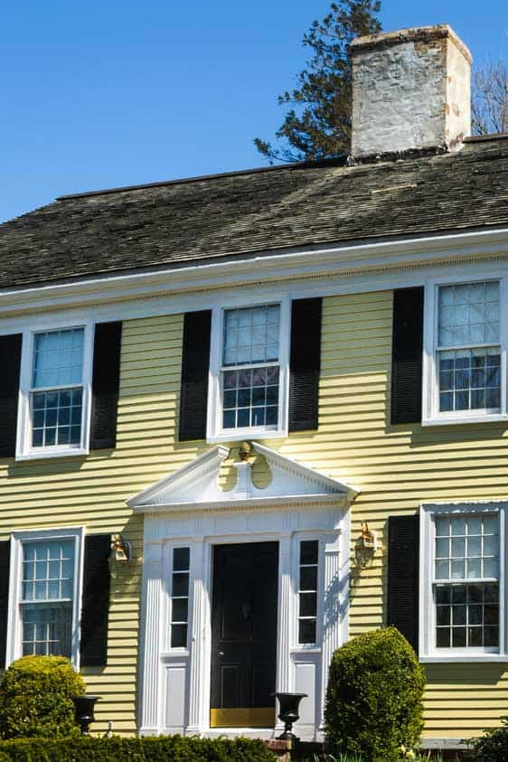 A beautifully maintained yellow home with brown doors