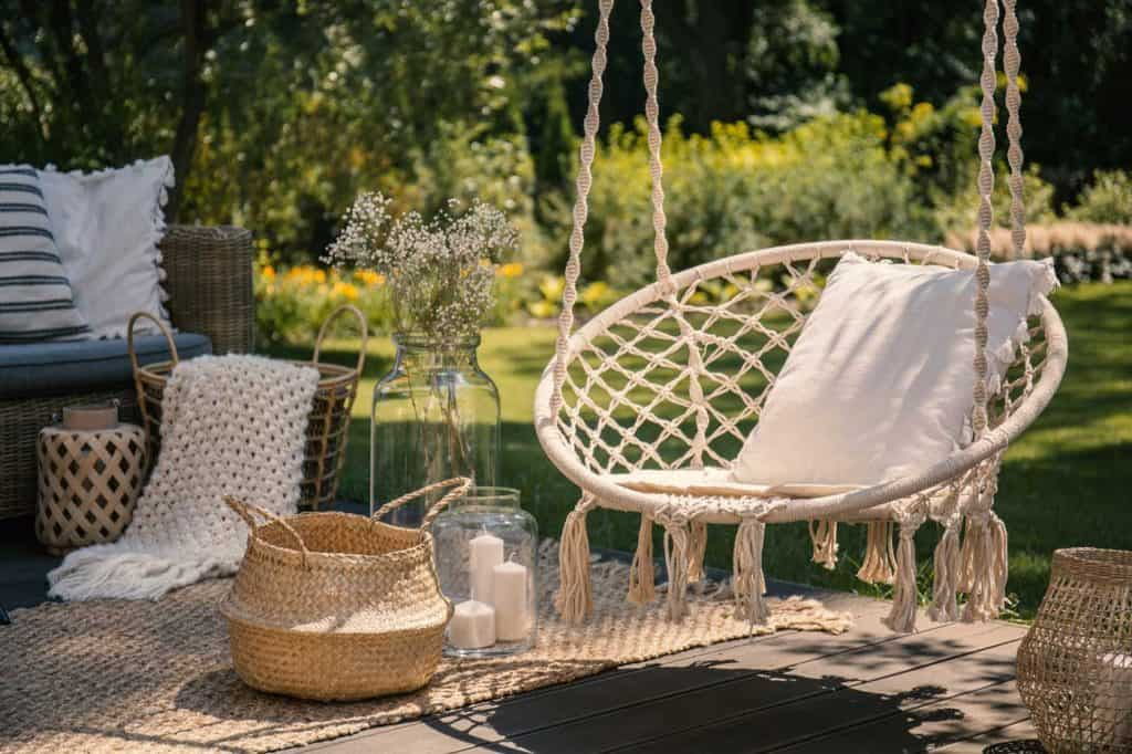 A beige string swing with a pillow on the front porch. Wicker baskets, a rug and a blanket on a wooden deck in the garden.