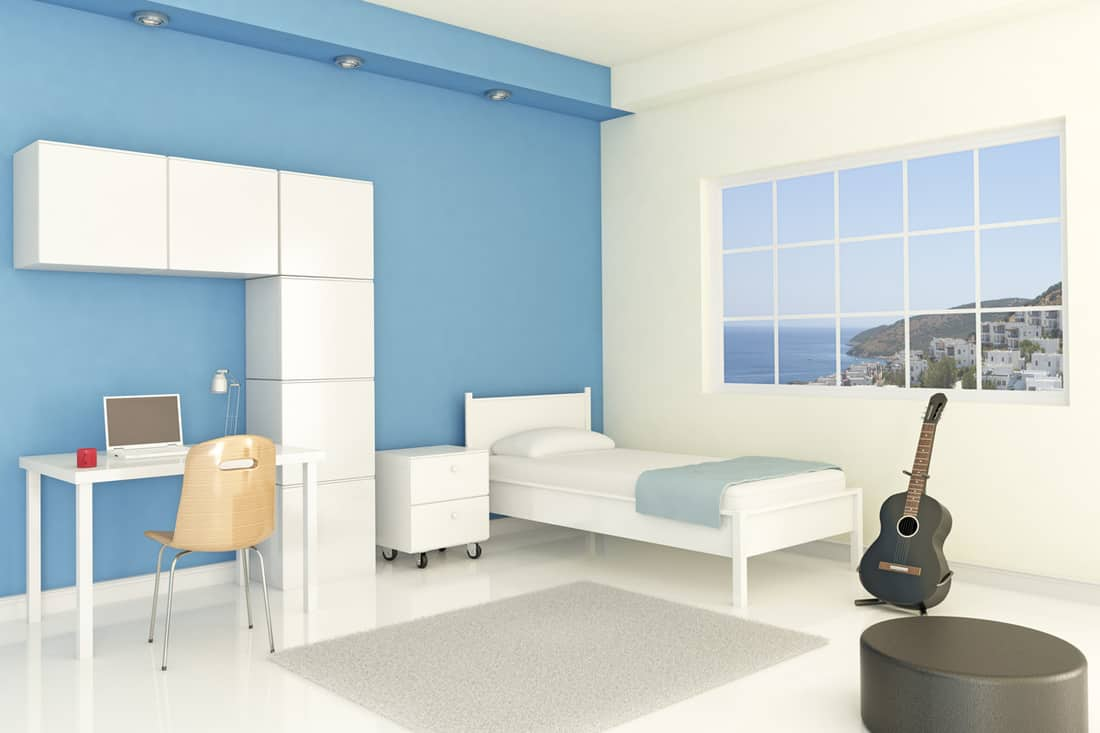 A blue and white colored bedroom with a large window and computer set on the side