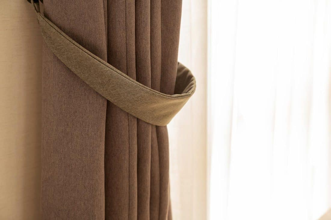 A brown curtain with a lace and a beige wall