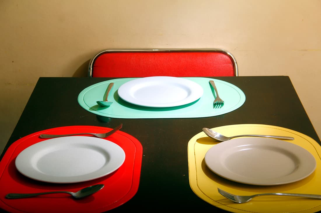 A brown wall with red, cyan, and yellow colored paper plates