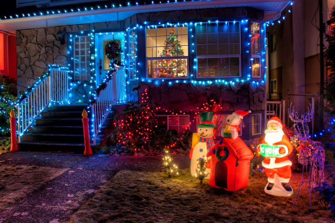 A Christmas decorated house with blue lighting at the porch and Santa at the front lawn