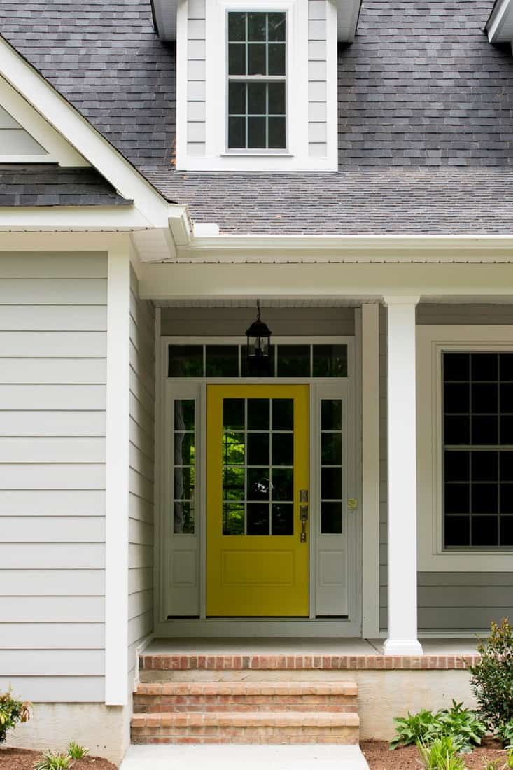 A classic colonial house with lots of windows and a yellow door