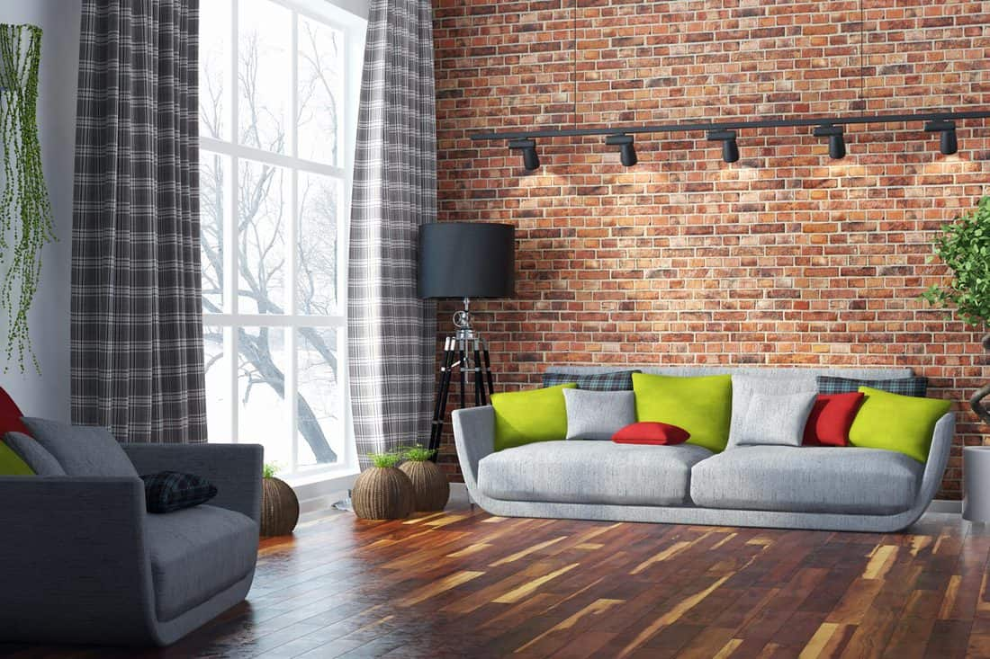 A living room with a wooden flooring, a brick walled cladding, and a huge window with a stripped curtain