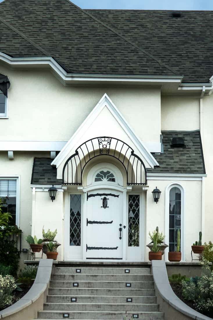 A luxurious white mansion with a white door and beautiful front garden