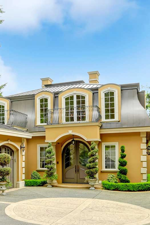 A luxury yellow mansion with brownish double doors and three parking garage