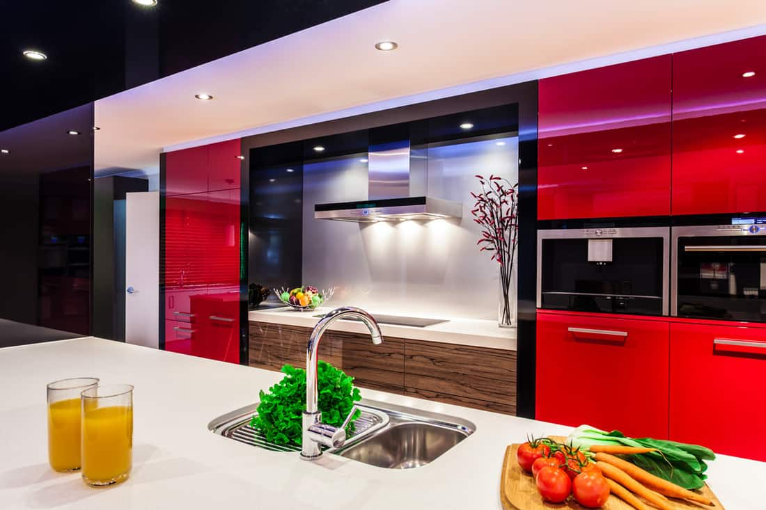 A modern kitchen with red colored cabinets, white granite island with sink, and expensive four burner with range hood