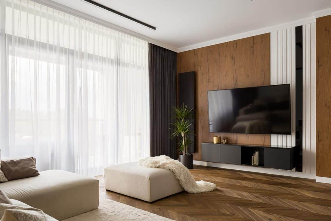 A modern living room with a beautiful furniture, and a wooden wall with black and white curtains