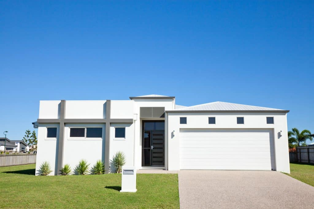A modern single storey house with a two cargo garage and a black door