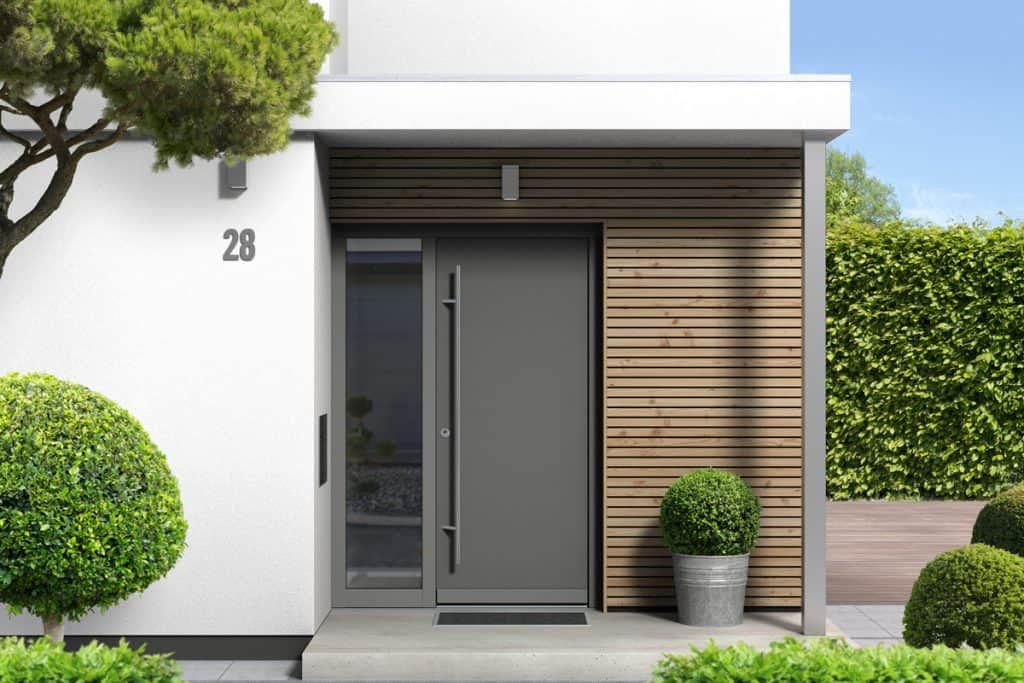 A porch of a contemporary house with gray aluminum door and a trellis like cladding