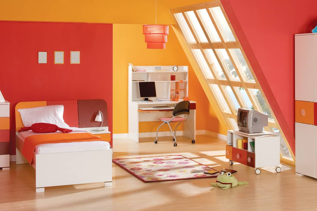 A Red and yellow colored bedroom with white colored furniture's and brown flooring