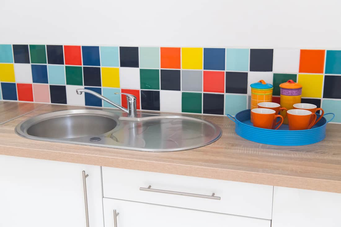 A sink with wooden countertop and colorfull square decorative tiles on the side