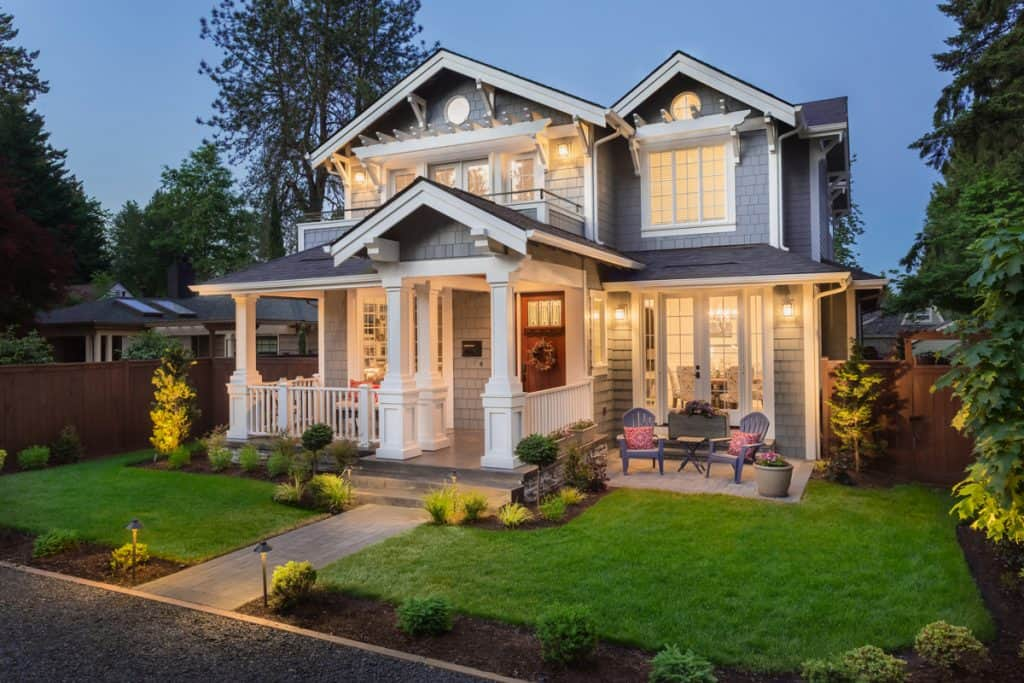 A two storey colonial house with a beautiful front porch, brown door, and windows