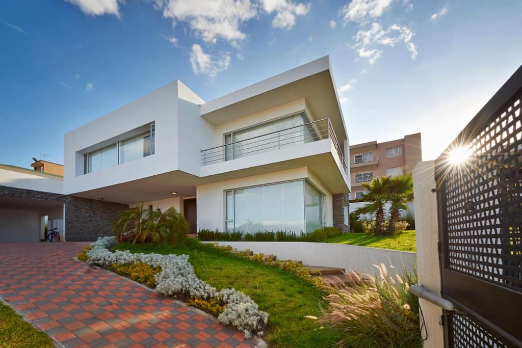 A two storey modern colonial house with a brown door with huge windows and a beautiful driveway