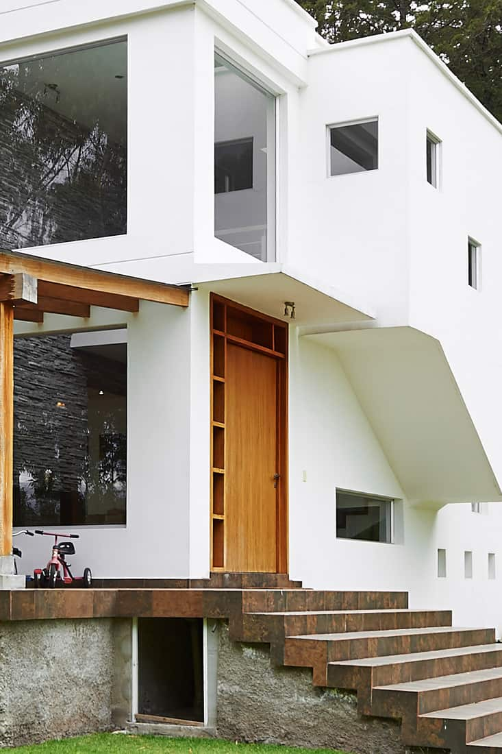 A two storey modern contemporary house with white painted walls and a brown front door