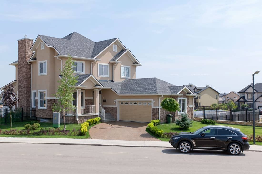 A two storey modern house with light brown color and roof shingles