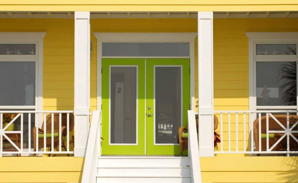 A very colorful entrance way to a yellow home with green doors in Pensacola Florida