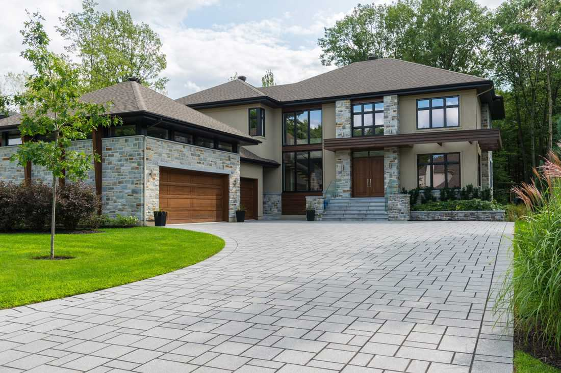 A very luxurious modern house with decorative stone cladding, cool driveway, and a two way double door