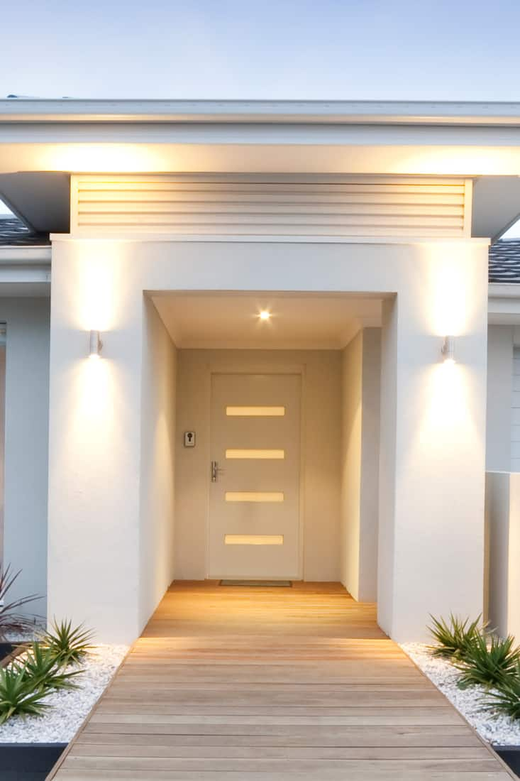 A white modern contemporary house with a gorgeous entry way with gorgeous brown door