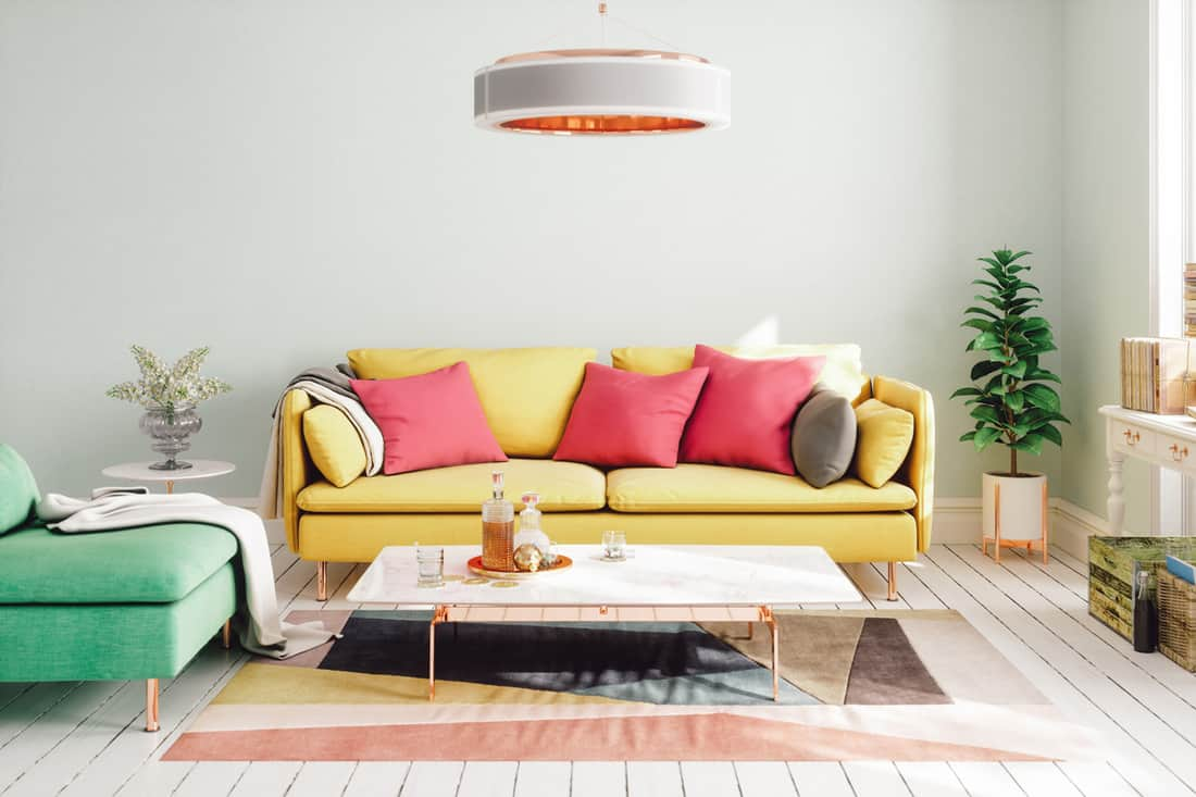 A white walled living room with a yellow sofa and colored throw pillows
