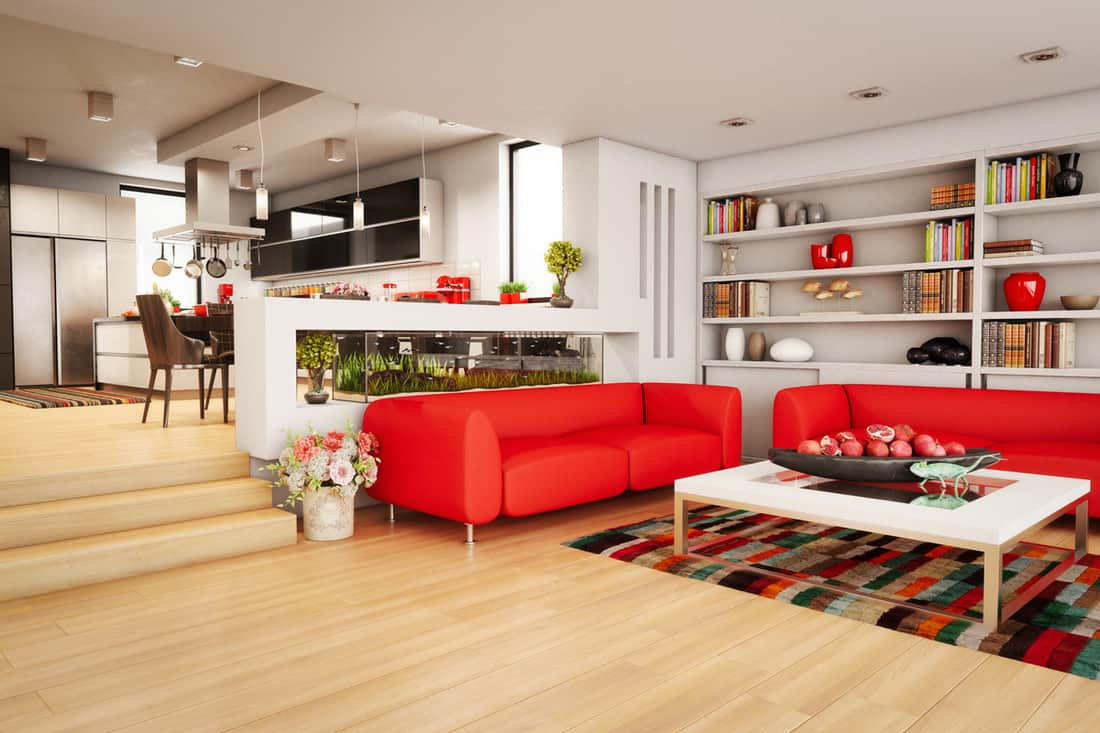 A wide living room with red colored sofa, white cabinets, and a dining room at the back