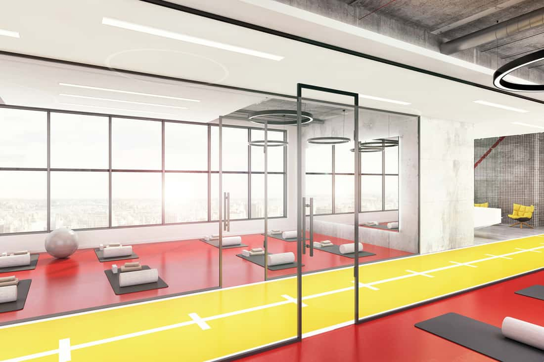 A yoga gym with red colored flooring, gray exercising mats, and pinks colored hot dog pillows