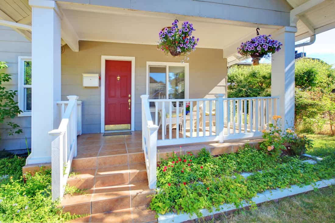 Beautiful front porch with hanging flowers and red door